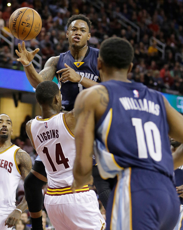 . Memphis Grizzlies\' Jarell Martin (1) passes over Cleveland Cavaliers\' DeAndre Liggins (14) to Troy Williams (10) in the second half of an NBA basketball game Tuesday, Dec. 13, 2016, in Cleveland. The Cavaliers won 103-86. (AP Photo/Tony Dejak)