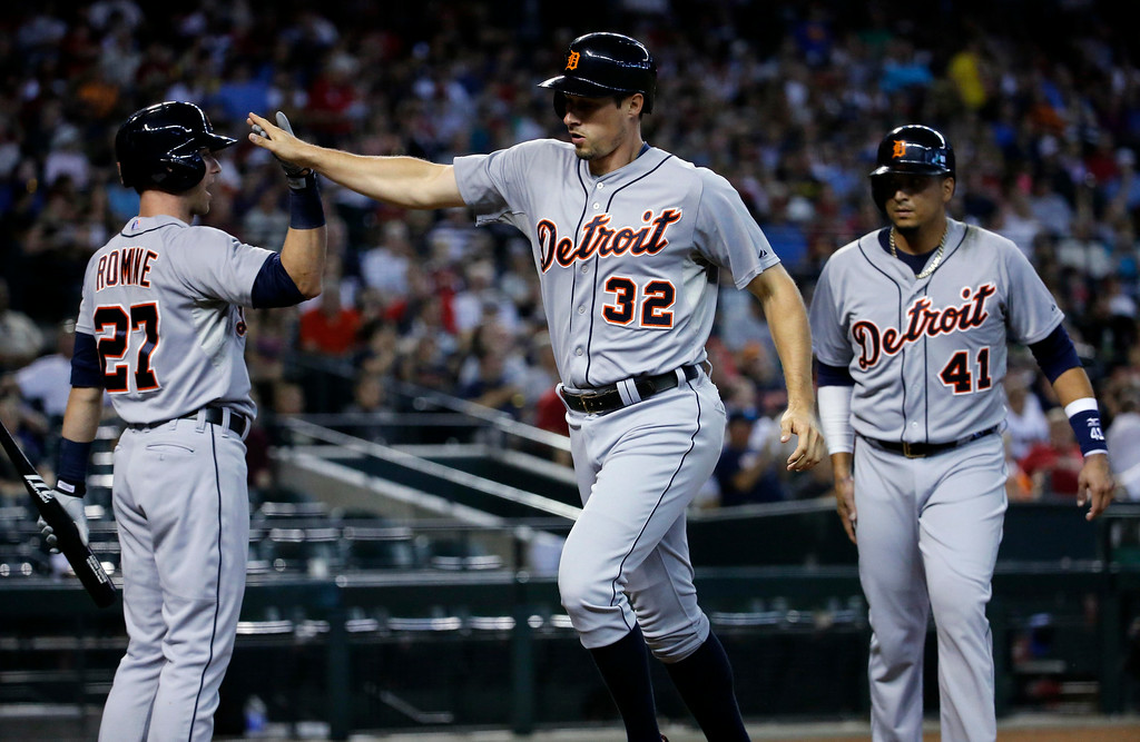 . Detroit Tigers\' Don Kelly (32) high fives teammate Andrew Romine (27) after scoring on a two-RIB double by teammate Alex Avila against the Arizona Diamondbacks during the second inning of a baseball game, Wednesday, July 23, 2014, in Phoenix. (AP Photo/Matt York)