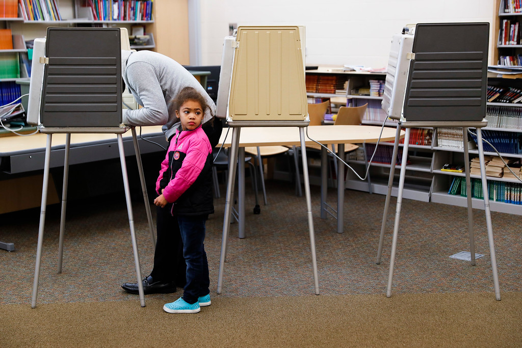 . A child waits while her guardian fills out a ballot at a polling station located in the Taft Information Technology High School, Tuesday, Nov. 7, 2017, in Cincinnati. Ohio voters will decide ballot issues on Tuesday that would place limits on drug prices and expand victims\' rights in criminal proceedings, along with several mayoral races. (AP Photo/John Minchillo)
