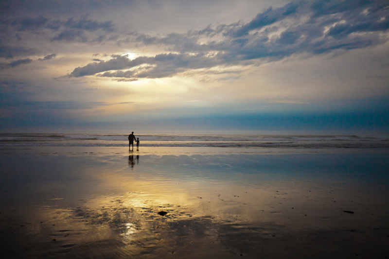 A father and son watch the sunset while vacationing at Rockaway Beach, Oregon.