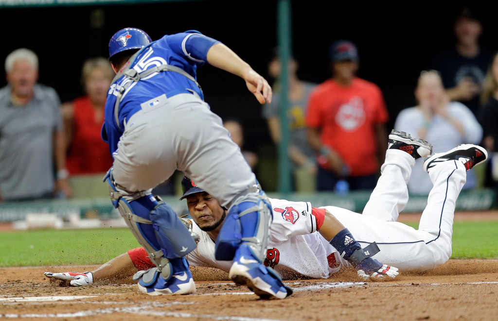 . Cleveland Indians\' Edwin Encarnacion is tagged out at home plate by Toronto Blue Jays catcher Russell Martin during the fourth inning of a baseball game, Friday, July 21, 2017, in Cleveland. (AP Photo/Tony Dejak)