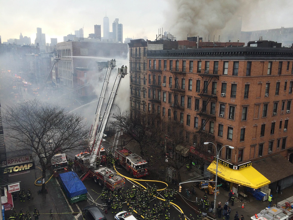 . Smoke billows from a building in New York\'s East Village neighborhood at the scene of a large fire and a partial building collapse Thursday, March 26, 2015. Orange flames and black smoke billowed from the facade and roof of the building in Manhattan, near several New York University buildings and the Washington Square Park area. (AP Photo/John Minchillo)