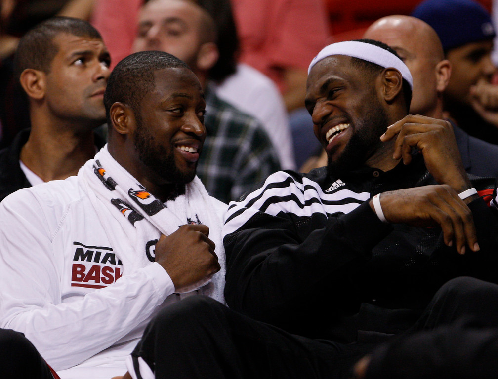 . Miami Heat guard Dwyane Wade, left, and forward LeBron James share a laugh as they sit on the bench during the second half of an NBA preseason basketball game against the Orlando Magic, Sunday, Dec. 18, 2011, in Miami. The Heat defeated the Magic 118-85. (AP Photo/Wilfredo Lee)