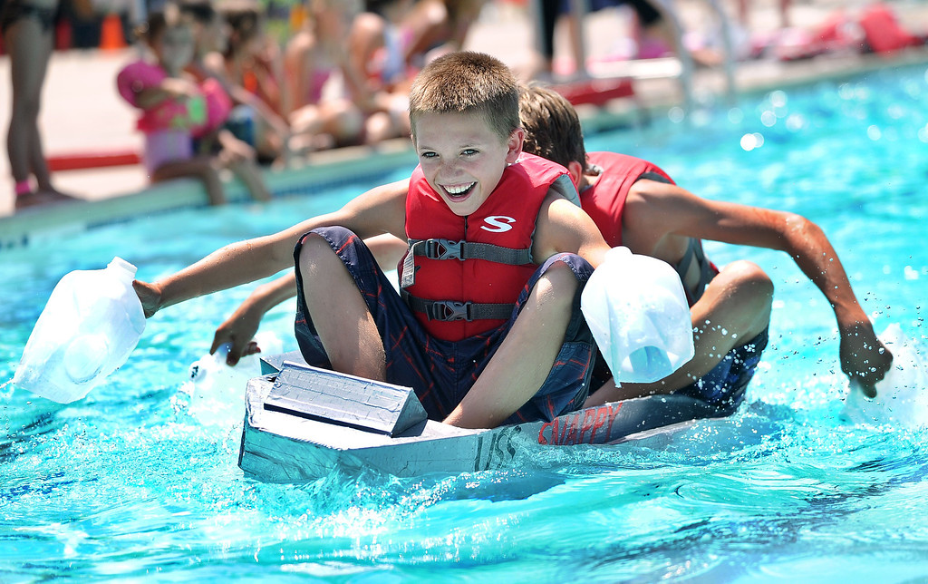 """. Cole Erny, 11, left, and his brother Harrison Erny, 13, of Orinda, paddle across a pool in their watercraft named \""""USS Snappy\"""" made of only cardboard, recyclables and duct tape during the Derby Day boat race held at Pleasant Hill Aquatic Park in Pleasant Hill, Calif., on Friday, July 19, 2013. (Doug Duran/Bay Area News Group)"""