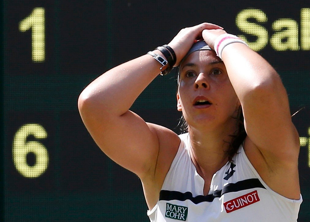 . Marion Bartoli of France reacts as she defeats Sabine Lisicki of Germany in their women\'s singles final tennis match at the Wimbledon Tennis Championships, in London July 6, 2013.      REUTERS/Suzanne Plunkett