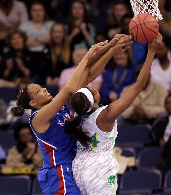 . Kansas forward Carolyn Davis, left, and Notre Dame forward Ariel Braker (44) battle for a rebound during the first half of a regional semi-final of the NCAA college basketball tournament Sunday  March 31, 2013, in Norfolk, Va.  (AP Photo/Steve Helber)
