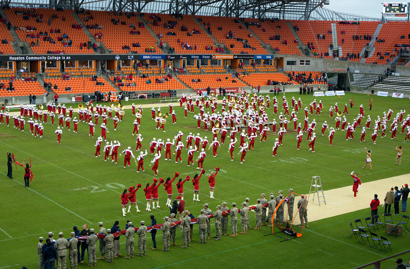 A big American flag is rolled up, about to be opened.  The band is running from one formation to the next ...