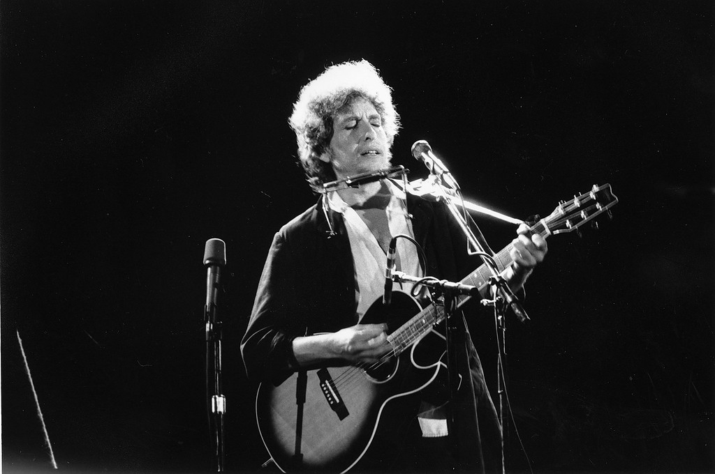 . This is an undated photo of singer-songwriter Bob Dylan as he plays his acoustic guitar with his harmonica at an unknown location.  (AP Photo)