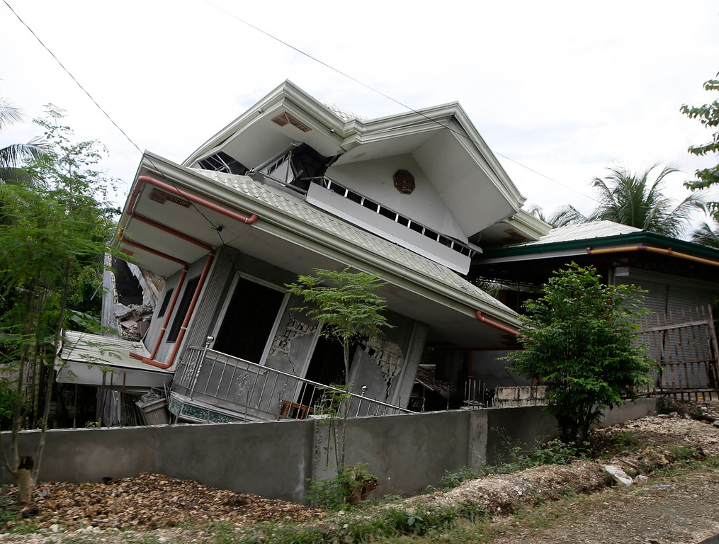 . A two-story house leans on its side Thursday Oct.17, 2013 after being damaged by a strong earthquake Tuesday in Maribojoc township, Bohol province in central Philippines.  (AP Photo/Bullit Marquez)
