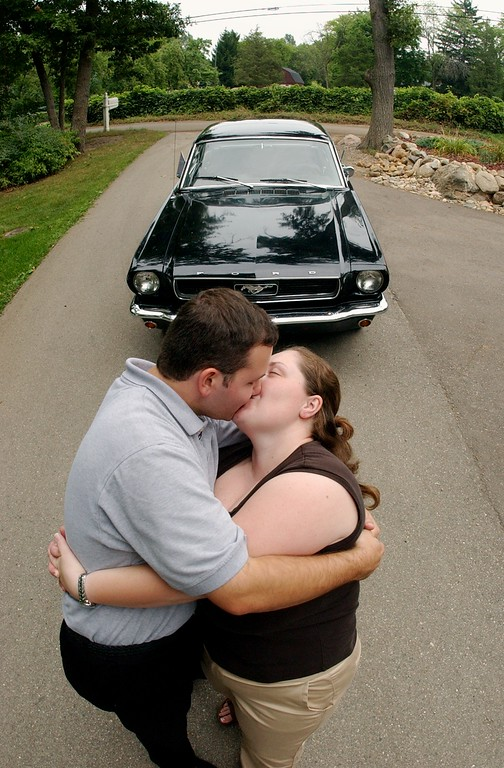 . Bryan Crandall, left, kisses his fiance, Michelle Barnett, in front of his father\'s 1966 Mustang, which they will drive after their wedding on Saturday, along the Dream Cruise route.  Photo taken on Thursday, August 18, 2005, in Waterford, Mich.