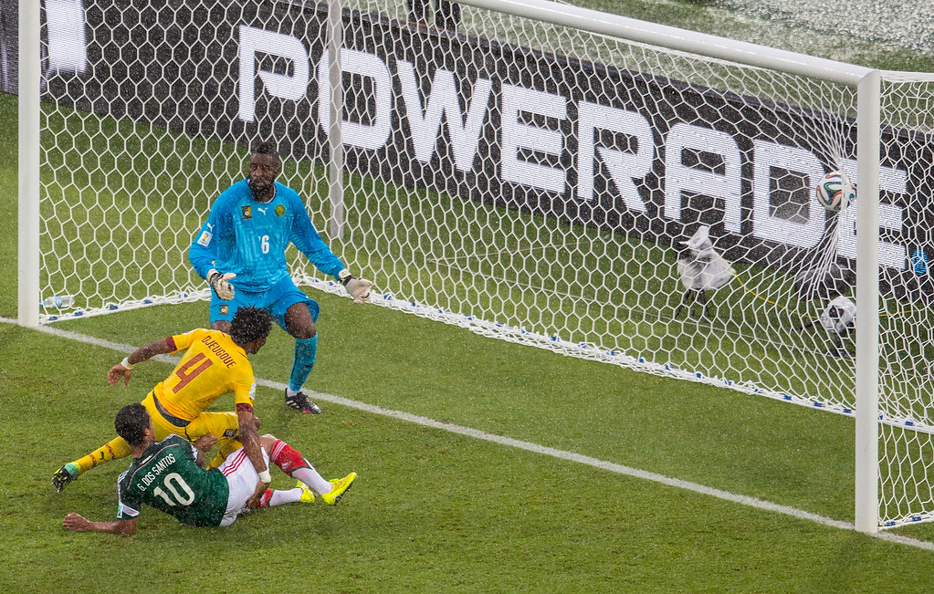 . Giovani dos Santos of Mexico puts the ball in the net but the goal was disallowed due to an offsides call as goalie Charles Itandje and Cedric Djeugoue of Cameroon looks on in the first half during the 2014 FIFA World Cup Brazil Group A match between Mexico and Cameroon at Estadio das Dunas on June 13, 2014 in Natal, Brazil.  (Photo by Miguel Tovar/Getty Images)