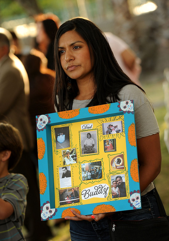 . Angelina Martinez, 29, holds a photo collage of her father Christopher Martinez during the annual Victims Candlelight Vigil at the police station in San Bernardino April 23, 2013.  Martinez was shot and killed March 28, 2012 along Highland Avenue in San Bernardino.  GABRIEL LUIS ACOSTA/STAFF PHOTOGRAPHER.