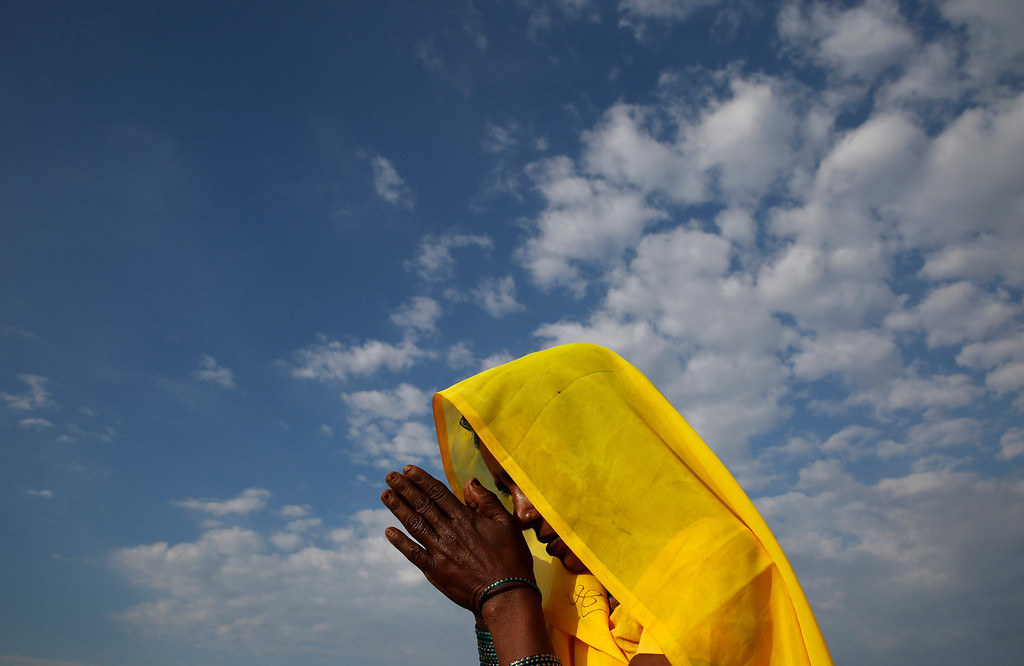 """. A Hindu devotee offers prayers at \'Sangam\', the confluence of rivers of Ganges and Yamuna during the \""""Shivaratri\"""" festival in Allahabad, India, Thursday, Feb. 27, 2014.  (AP Photo/Rajesh Kumar Singh)"""