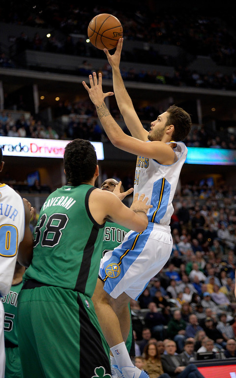 . Denver Nuggets shooting guard Evan Fournier (94) takes a shot over Boston Celtics center Vitor Faverani (38) during the second quarter January 7, 2014 at Pepsi Center. (Photo by John Leyba/The Denver Post)