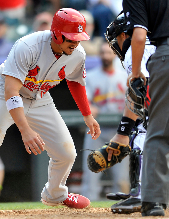 . St. Louis Cardinals\' Jon Jay (19) tries to get past Colorado Rockies catcher Yorvit Torrealba to home plate during the ninth inning of a baseball game on Thursday, Sept. 19, 2013, in Denver. Jay was tagged out at home by Torrealba. (AP Photo/Jack Dempsey)