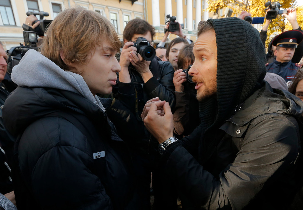 . A gay rights activist, left, argues with an anti-gay protester during an authorized gay rights rally in St.Petersburg, Russia, Saturday, Oct. 12, 2013. A gay rights rally in St. Petersburg has ended in scuffles after several dozen protesters were confronted by about 200 conservative and religious activists. The police standing nearby waited until clashes broke out between the two groups before intervening. According to Russian news agencies, the police detained 67 people from both sides. (AP Photo/Dmitry Lovetsky)