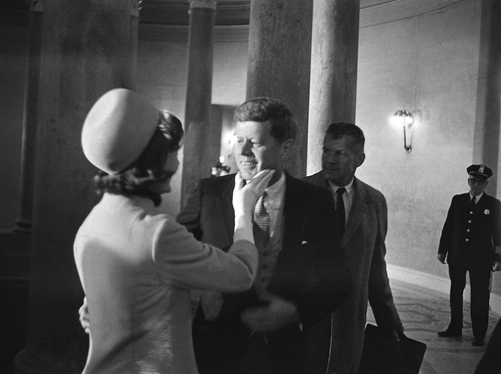 . ** FILE ** In this Jan. 20, 1961 file photo, Jacqueline Kennedy, left, has a chuck under the chin for her husband, President John F. Kennedy, moments after he became president. This exclusive picture by AP photographer Henry Burroughs was taken in the rotunda of the Capitol just after Kennedy left the inaugural stand. (AP Photo/Henry Burroughs, File)
