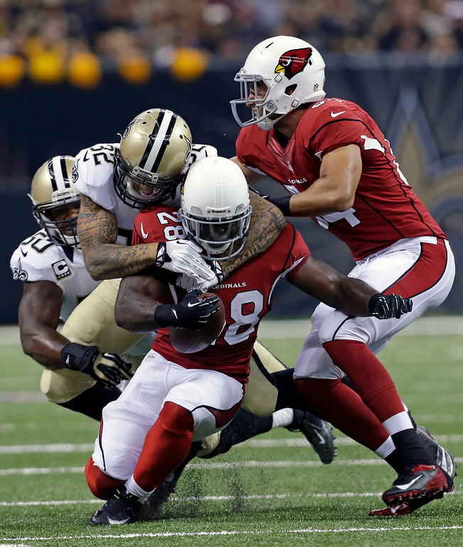 . Arizona Cardinals running back Rashard Mendenhall (28) is tackled by New Orleans Saints strong safety Kenny Vaccaro (32) and middle linebacker Curtis Lofton (50) in the first half of an NFL football game in New Orleans, Sunday, Sept. 22, 2013. (AP Photo/Gerald Herbert)