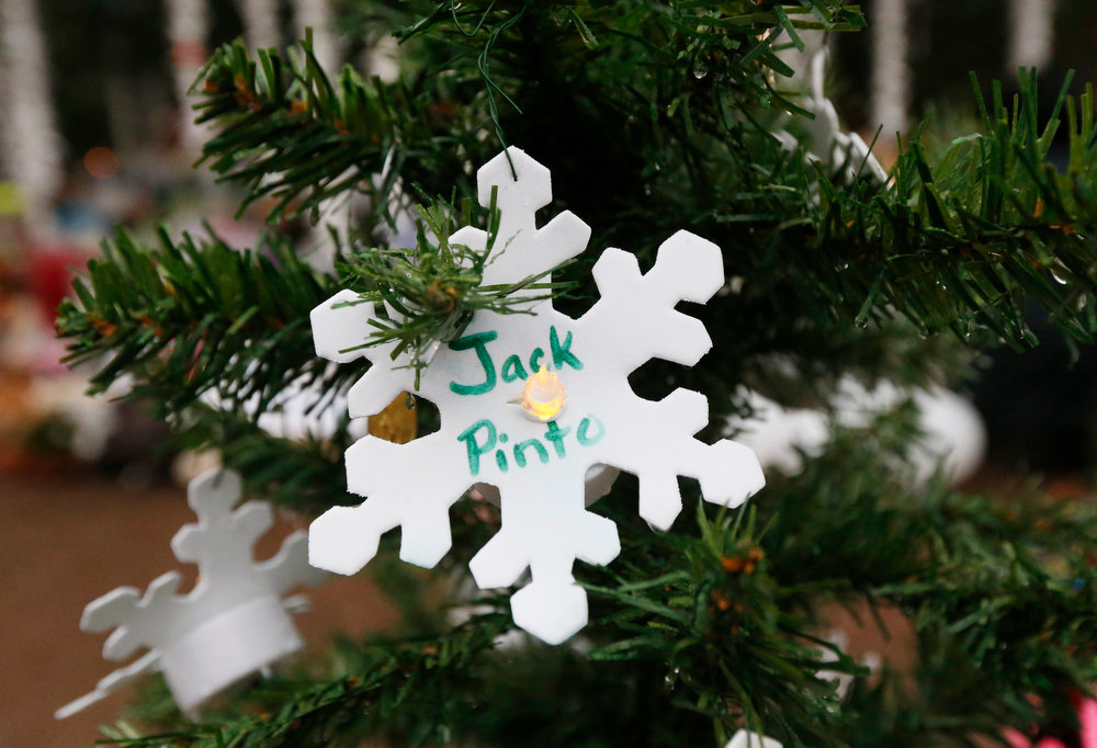 Description of . A snowflake ornament with the name of 6-year-old Jack Pinto hangs on a Christmas tree at a makeshift memorial in the Sandy Hook village of Newtown, Conn., Monday, Dec. 17, 2012, as the town mourns victims killed in Friday's school shooting. Pinto, who was killed Friday when gunman Adam Lanza opened fire inside the Sandy Hook Elementary School, will be buried Monday. (AP Photo/Julio Cortez)