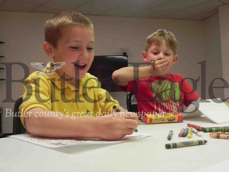 Caleb Anderson, 6, Quinn Warheit, 6, and Dylan Campbell, 9, cut out dough to form dog treats for the Butler County Humane Society. Photo by Gabriella Canales.
