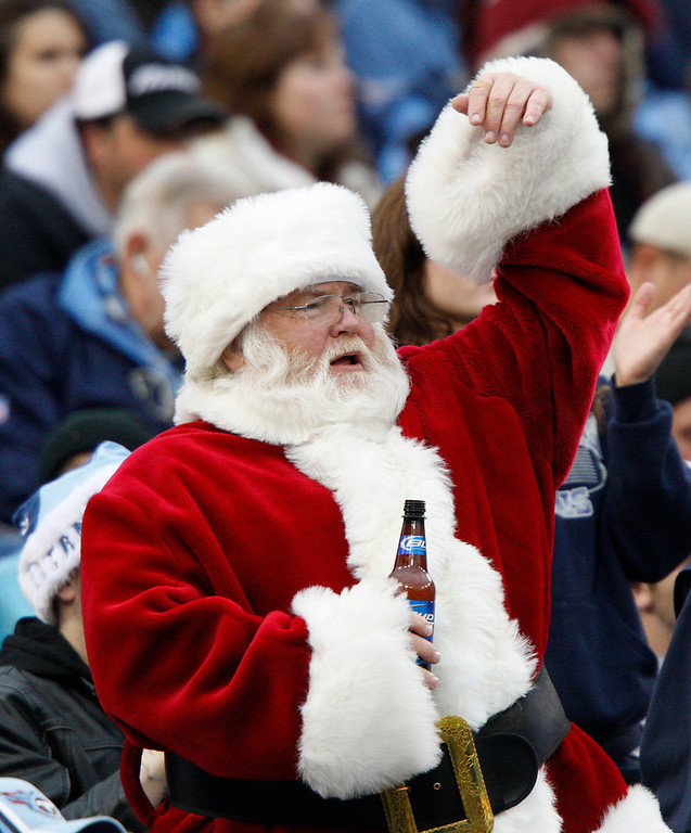 . A Tennessee Titans fan dressed as Santa Claus holds his beer as he cheers in the first quarter of an NFL football game against the St. Louis Rams on Sunday, Dec. 13, 2009, in Nashville, Tenn. (AP Photo/Wade Payne)