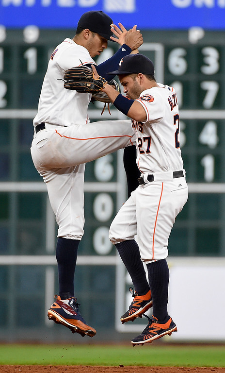 . Houston Astros second baseman Jose Altuve (27) and shortstop Carlos Correa celebrate the Astros\' 7-1 victory over the Cleveland Indians in a baseball game, Monday, May 9, 2016, in Houston. (AP Photo/Eric Christian Smith)
