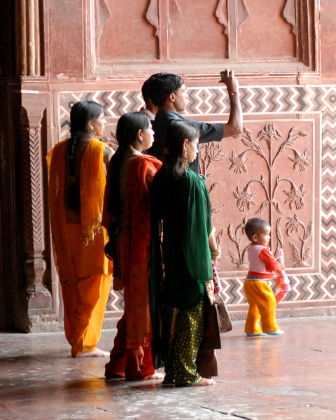 A family looking out of the guest house towards the mausoleum at Taj Mahal.  Beautiful colors.