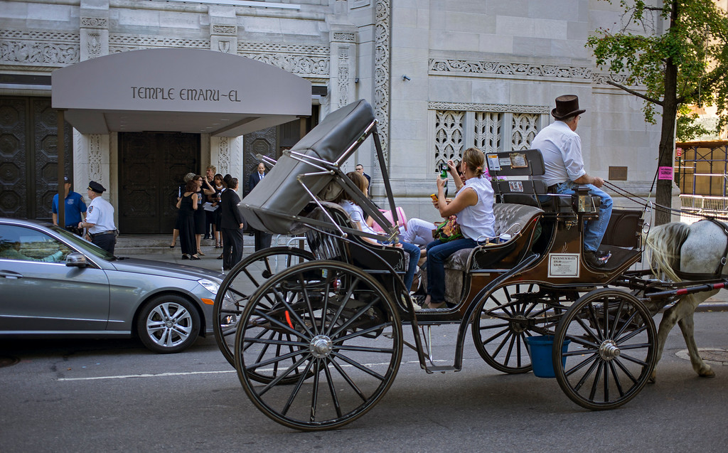 . People in a horse and carriage pass as attendees arrive at a funeral service for comedian Joan Rivers at Temple Emanu-El in New York, Sunday, Sept. 7, 2014. Rivers died Thursday, Sept. 4, 2014. She was 81. (AP Photo/Craig Ruttle)