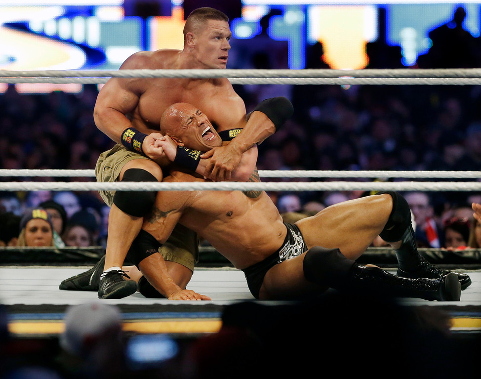. Wrestler John Cena, top, chokes Dwayne Douglas Johnson, known as The Rock as they wrestle Sunday, April 7, 2013, in East Rutherford, N.J., during Wrestlemania. (AP Photo/Mel Evans)