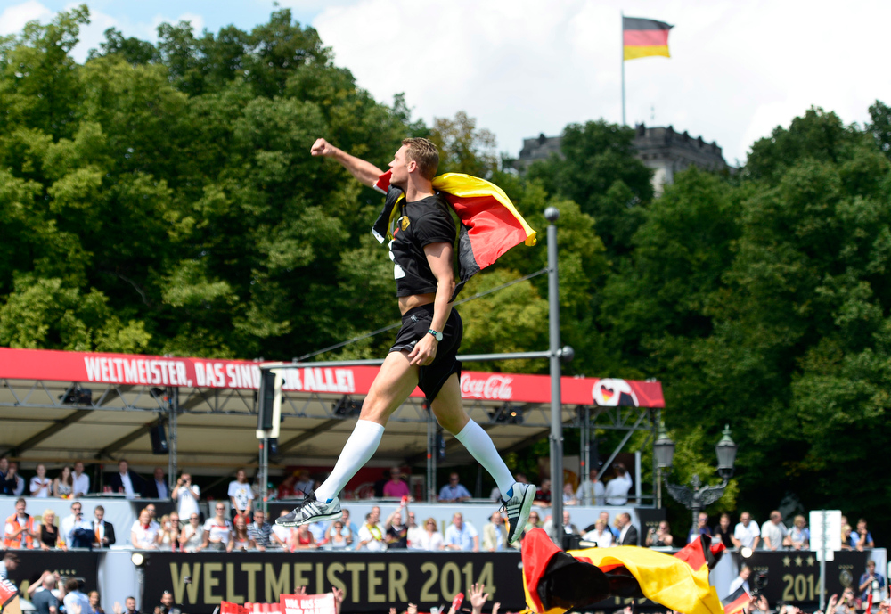 . Goalkeeper Manuel Neuer is airborne during a fan party after the arrival of the German national soccer team in Berlin Tuesday, July 15, 2014. Germany beat Argentina 1-0 on Sunday to win its fourth World Cup title.  In background is the Reichstag building. (AP Photo/Jens Meyer)