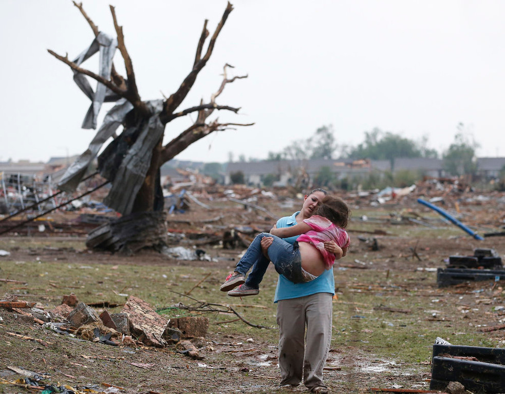 . A woman carries her child through a field near the collapsed Plaza Towers Elementary School in Moore, Okla., Monday, May 20, 2013. A tornado as much as a mile (1.6 kilometers) wide with winds up to 200 mph (320 kph) roared through the Oklahoma City suburbs Monday, flattening entire neighborhoods, setting buildings on fire and landing a direct blow on an elementary school. (AP Photo Sue Ogrocki)