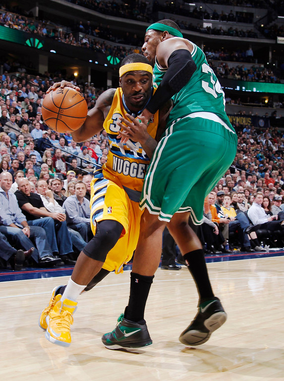 . Denver Nuggets guard Ty Lawson, left, is fouled while driving to the basket by Boston Celtics forward Paul Pierce in the fourth quarter of the Nuggets\' 97-90 victory in an NBA basketball game in Denver on Tuesday, Feb. 19, 2013. (AP Photo/David Zalubowski)