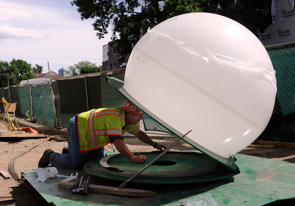. Randy Mansfield from Peak Custom Fabrication prepares the large white bulb before it is placed on the sculpture, Tuesday, June 25, 2013.  (Photo By Kathryn Scott Osler/The Denver Post)