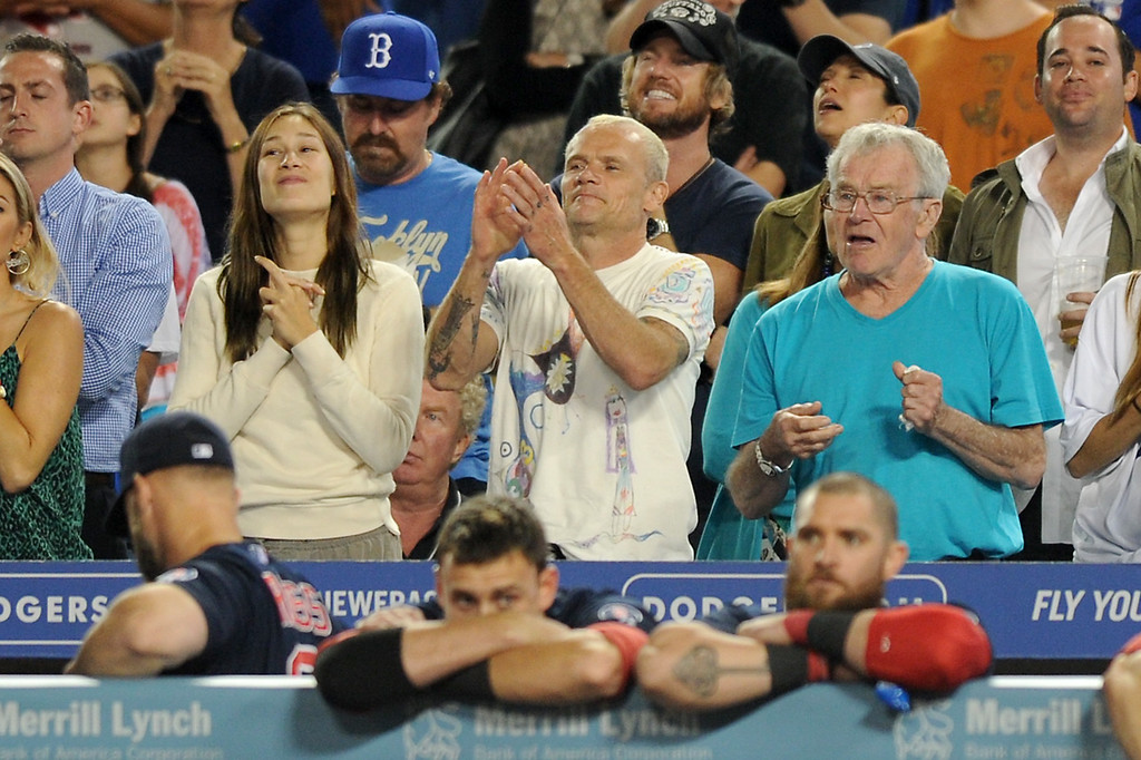 . Red Hot Chili Peppers\' Flea, center, cheers as the Dodgers beat the Red Sox 2-0, Friday, August 23, 2013. (Michael Owen Baker/L.A. Daily News)