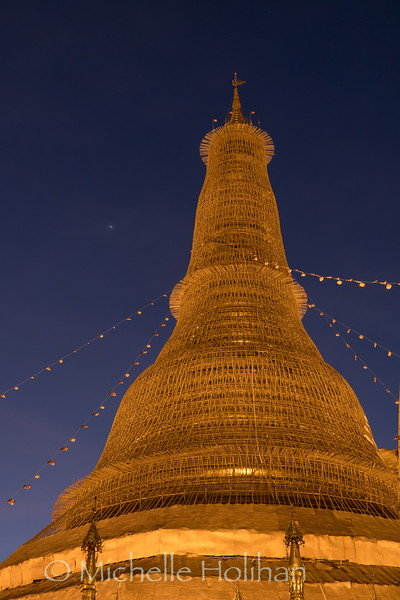 Dawn at the main shrine of Shwedagon Pagoda covered with scaffolding for painting in Yangon, Myanmar