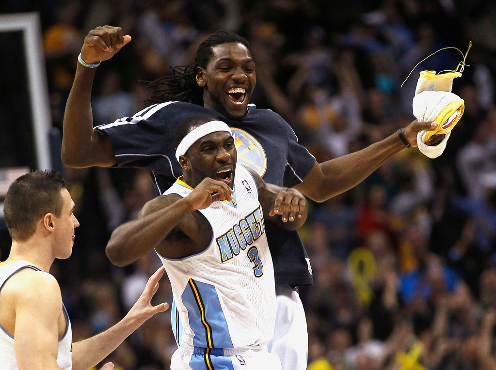 . Denver Nuggets\' Ty Lawson (C) celebrates scoring the game winning basket with teammate Kenneth Faried (top) over the Oklahoma City Thunder in their NBA basketball game in Denver March 1, 2013. REUTERS/Rick Wilking