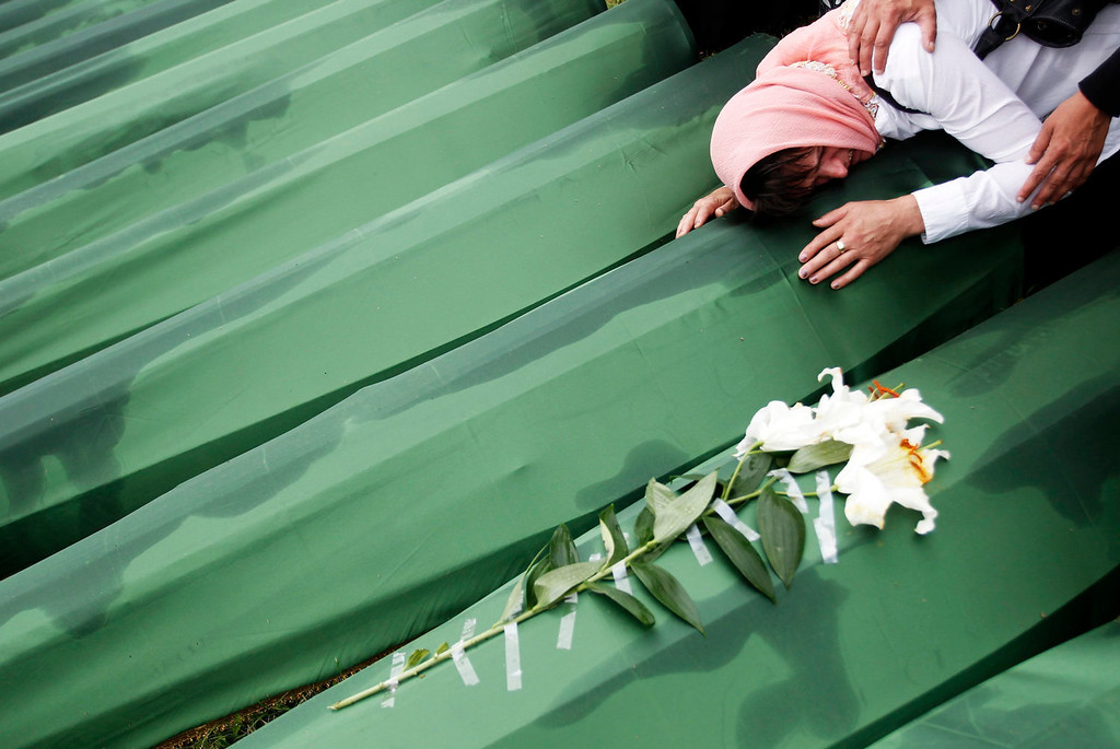 . A Bosnian woman cries on the coffin of a relative, which is one of the 409 coffins of newly identified victims from the 1995 Srebrenica massacre, in Potocari Memorial Center, near Srebrenica July 11, 2013. The bodies of the recently identified victims will be transported to the memorial centre in Potocari where they will be buried on July 11 marking the 18th anniversary of the massacre in which Bosnian Serb forces commanded by Ratko Mladic killed up to 8,000 Muslim men and boys and buried them in mass graves. REUTERS/Dado Ruvic
