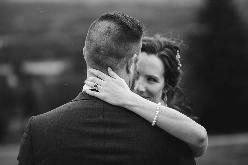 The bride holds the back of the grooms head as she looks devilishly into his eyes.