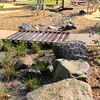 timber bridge and suspension bridge over creek bed with boulders