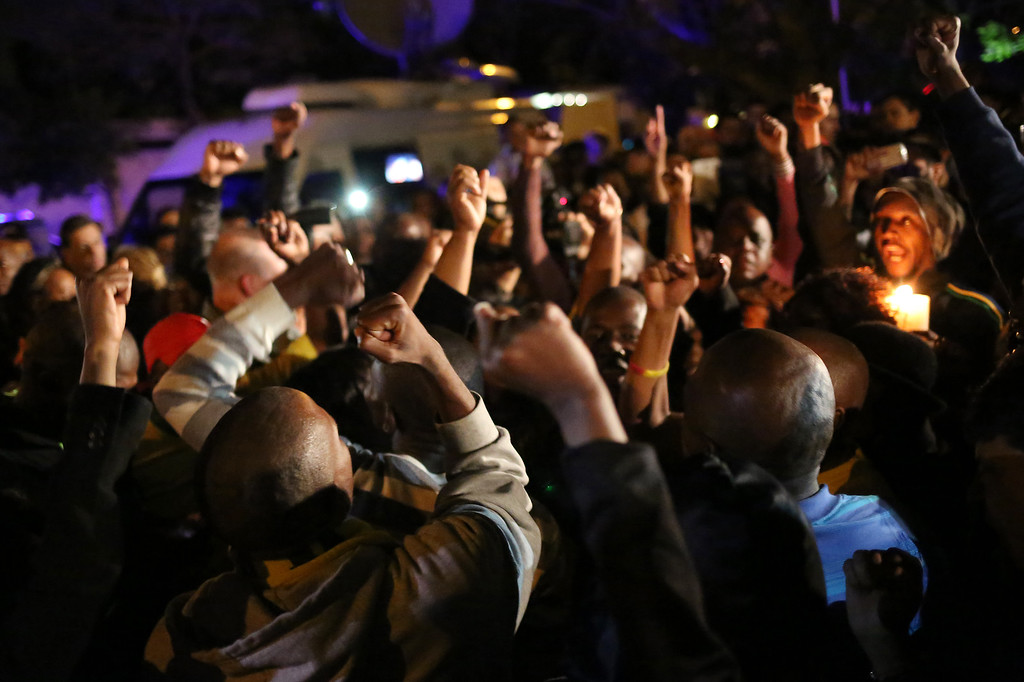 . South Africans react as they pay tribute to former South African president Nelson Mandela following his death in Johannesburg on December 5, 2013. Mandela, the revered icon of the anti-apartheid struggle in South Africa and one of the towering political figures of the 20th century, has died aged 95. Mandela, who was elected South Africa\'s first black president after spending nearly three decades in prison, had been receiving treatment for a lung infection at his Johannesburg home since September, after three months in hospital in a critical state.    (ALEXANDER JOE/AFP/Getty Images)
