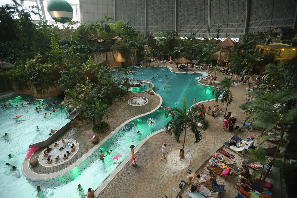 Description of . Visitors swim in the lagoon at the Tropical Islands indoor resort on February 15, 2013 in Krausnick, Germany. Located on the site of a former Soviet military air base, the resort occupies a hangar built originally to house airships designed to haul long-distance cargo. Tropical Islands opened to the public in 2004 and offers visitors a tropical getaway complete with exotic flora and fauna, a beach, lagoon, restaurants, water slide, evening shows, sauna, adventure park and overnights stays ranging from rudimentary to luxury. The hangar, which is 360 metres long, 210 metres wide and 107 metres high, is tall enough to enclose the Statue of Liberty.  (Photo by Sean Gallup/Getty Images)