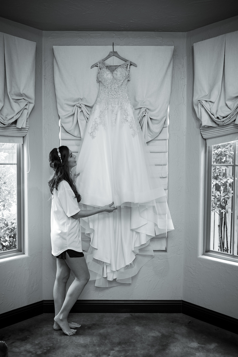a bride standing underneath her wedding dress as it hands on a window curtain rod