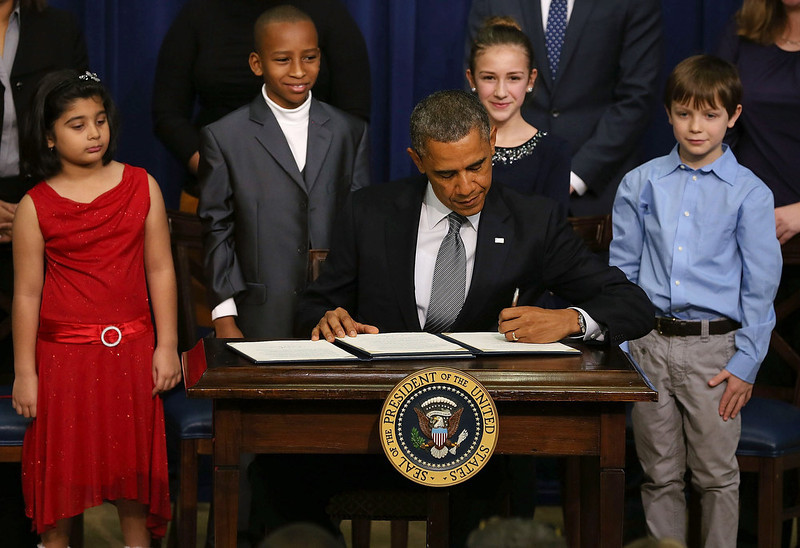 . U.S. President Barack Obama is flanked by young children as he signs a executive order designed to tackle gun control, on January 16, 2012 in Washington, DC. One month after a massacre that left 20 school children and 6 adults dead in Newtown, Connecticut, the president unveiled a package of gun control proposals that include universal background checks and bans on assault weapons and high-capacity magazines.  (Photo by Mark Wilson/Getty Images)
