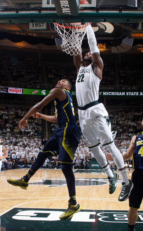 . Michigan State\'s Branden Dawson (22) goes up for a dunk over Michigan\'s Zak Irvin during the first half of an NCAA college basketball game, Sunday, Feb. 1, 2015, in East Lansing, Mich. Michigan State won 76-66 in overtime. (AP Photo/Al Goldis)