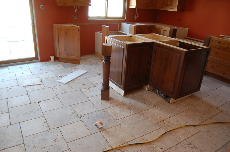 The floor of the kitchen; the post that will hold the granite counter looks lonely.