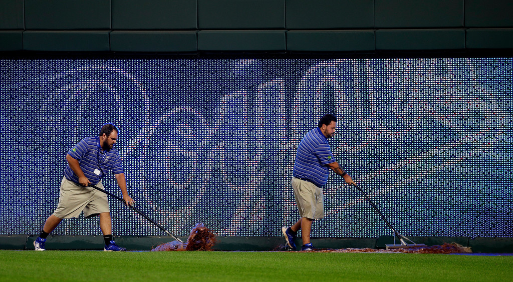 . Grounds crew workers roll water off the warning track during a delay during the fourth inning of a baseball game between the Kansas City Royals and the Cleveland Indians on Friday, Aug. 24, 2018, in Kansas City, Mo. The water was believed to come from a leak in a fountain in right field delaying the game for half an hour. (AP Photo/Charlie Riedel)