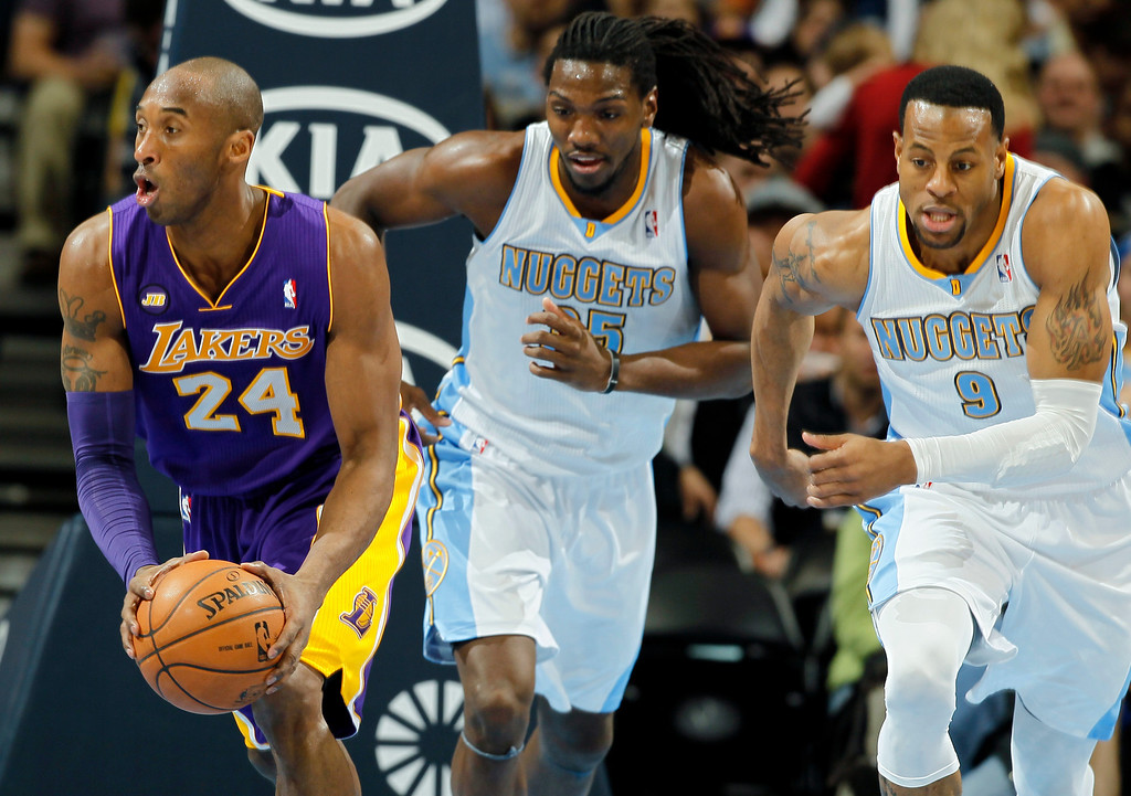 . Los Angeles Lakers guard Kobe Brant, left, picks up a loose ball in front of Denver Nuggets forward Kenneth Faried, center, and guard Andre Iguodala in the first quarter of an NBA basketball game in Denver on Monday, Feb. 25, 2013. (AP Photo/David Zalubowski)