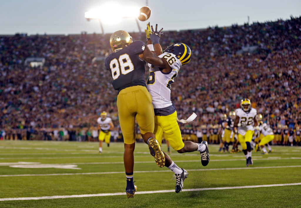. Michigan defensive back Jourdan Lewis, right, interferes with Notre Dame wide receiver Corey Robinson in as he attempts a catch in the end zone during the first half of an NCAA college football game in South Bend, Ind., Saturday, Sept. 6, 2014. (AP Photo/Michael Conroy)