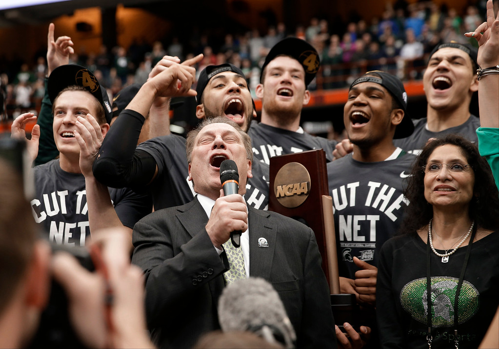 . Michigan State coach Tom Izzo celebrates with his team after the East Regional final against Louisville in the NCAA men\'s college basketball tournament Sunday, March 29, 2015, in Syracuse, N.Y. Michigan State won 76-70. (AP Photo/Seth Wenig)