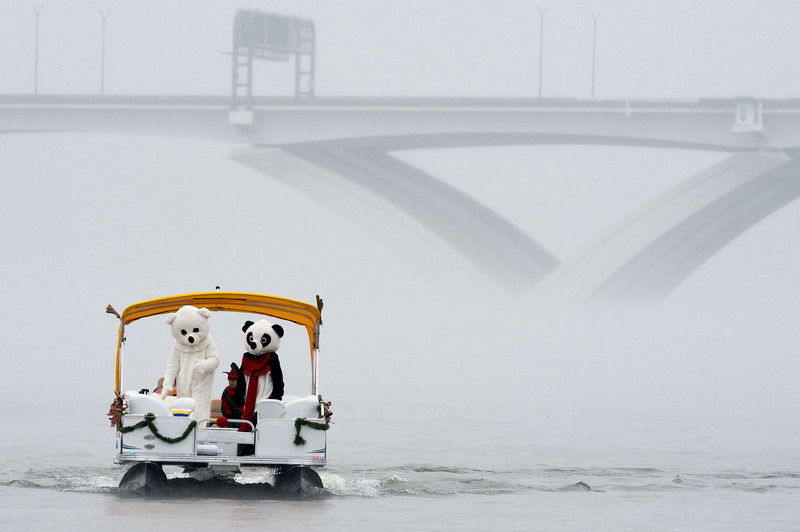 . A couple of costumed characters navigate up the Potomac River in a dinghy off Old Town Alexandria, Virginia, not far from Washington, DC December 24, 2014 during the annual water-skiing Santa event.    PAUL J. RICHARDS/AFP/Getty Images